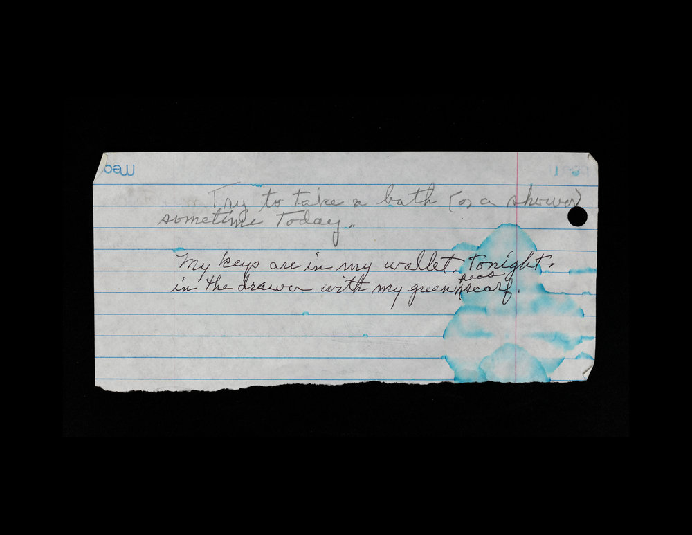 "Photograph of a torn piece of binder paper with pencil writing on a black background. The blue lines on the paper are blurred from a water stain in the bottom right. The writing in cursive reads ""Try to take a bath (or shower) sometime Today."" and on the next line ""My keys are in my wallet tonight in the drawer with my green scarf."""