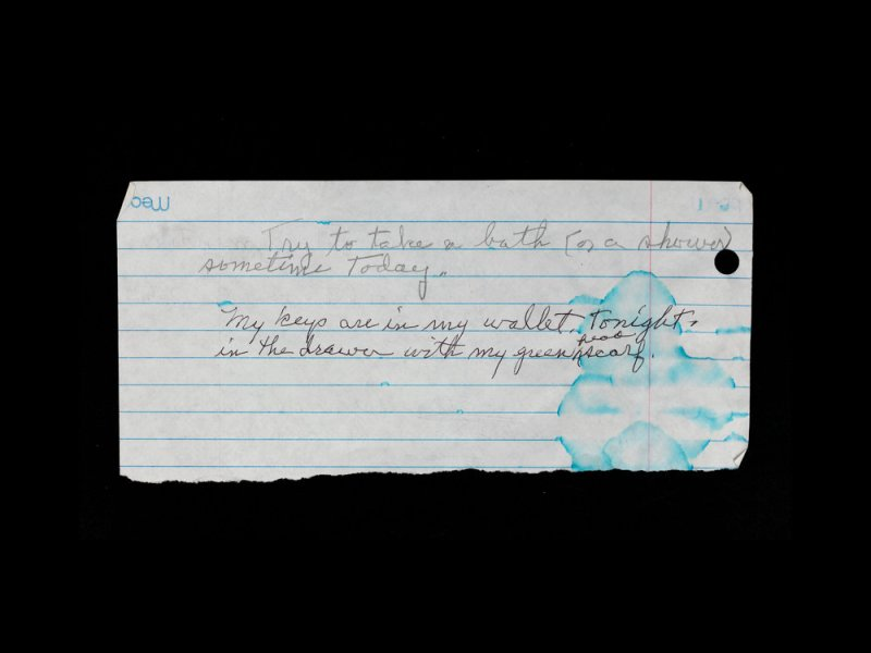 """Photograph of a torn piece of binder paper with pencil writing on a black background. The blue lines on the paper are blurred from a water stain in the bottom right. The writing in cursive reads """"Try to take a bath (or shower) sometime Today."""" and on the next line """"My keys are in my wallet tonight in the drawer with my green scarf."""""""
